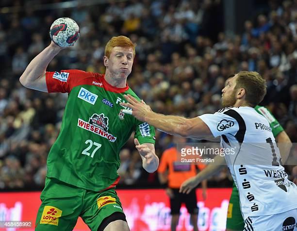 Steffen Weinhold of Kiel challenges for the ball with Tomasz Gebala of Magdeburg during the DKB Bundesliga handball match between THW Kiel and SC...