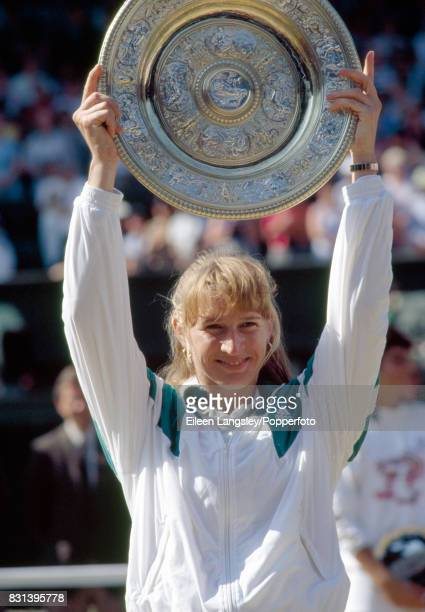 Steffi Graf of Germany holds the trophy aloft after her women's singles final win over Gabriela Sabatini of Argentina in three sets during the...