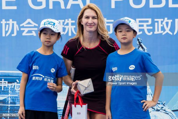 Steffi Graf of Germany the global ambassador of Zhuhai WTA Elite Trophy 2017 poses for photo with children during the tennis clinic at plaza of...