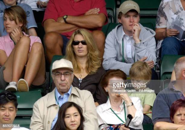 Steffi Graff and her son watch her husband Andre Agassi in action against Italy's Andreas Seppi during the second round of The All England Lawn...