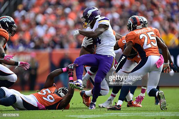Stefon Diggs of the Minnesota Vikings is tripped up by Danny Trevathan of the Denver Broncos on a short pass reception in the first quarter The...