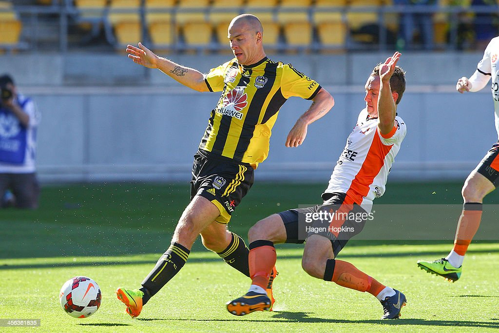 Stein Huysegems of the Phoenix beats the tackle of Matt Smith of the Roar during the round 10 A-League match between the Wellington Phoenix and Brisbane Roar at Westpac Stadium on December 14, 2013 in Wellington, New Zealand.