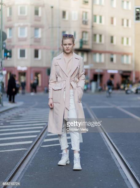Stella Kippe wearing a trench coat white denim jeans white boots cropped top sunglasses on March 26 2017 in Berlin Germany
