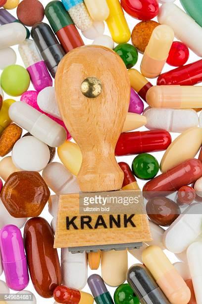 Stempel auf bunten Tabletten Symbolfoto für Krankheit Krankschreibung und Medikamente