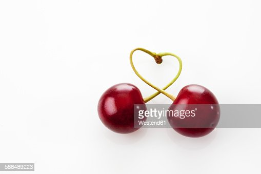 Stems of two sour cherries shaping a heart on white ground