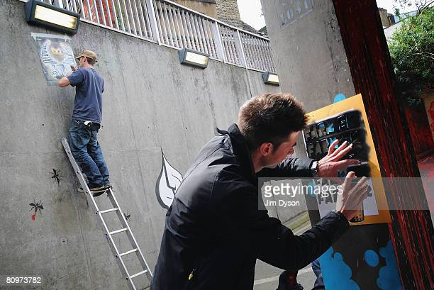 Stencil artists paint the walls of a subway as a giant new exhibition space created by famed graffiti artist Banksy opens to the public on May 3 2008...