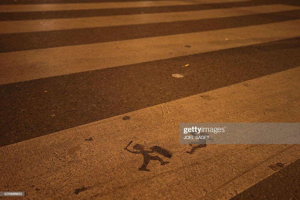A stencil is sprayed onto a zebra crossing close to the Place de la Republique in Paris where the Nuit Debout, or 'Up All Night' movement have been rallying against the French government's proposed labour reforms on April 29, 2016.