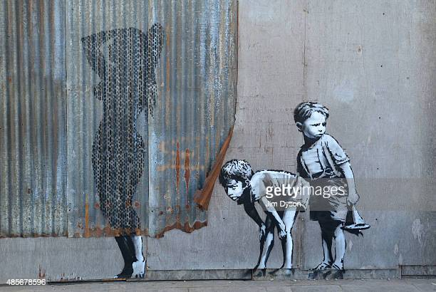 A stencil mural by Banksy depicting boys spying on a woman having a shower as Banksy's Dismaland Bemusement Park opens to the public on August 28...