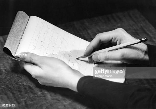 Stenographer's hands with pad and pencil