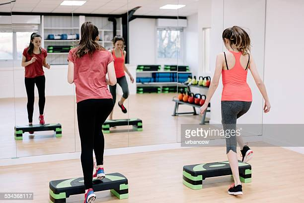 Step aerobics class in an exercise studio