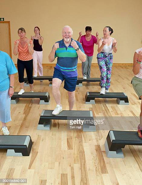 Step aerobics class, senior man in centre, smiling
