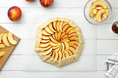 Step by step recipe galette or pie with nectarines. Dough with stuffing ready to bake. Cooking process top view.