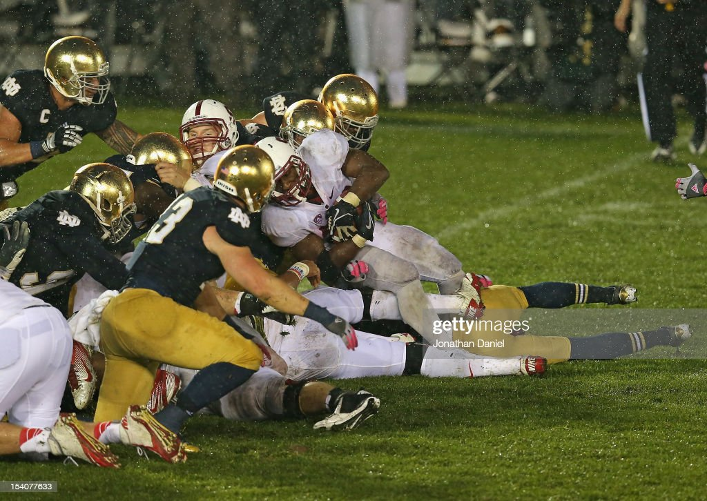 Stepfan Taylor #33 of the Stanford Cardinal is stopped short of the goal by members of the Notre Dame Fighting Irish defense on the last play of the game at Notre Dame Stadium on October 13, 2012 in South Bend, Indiana. Notre Dame defeated Stanford 20-13 in overtime.