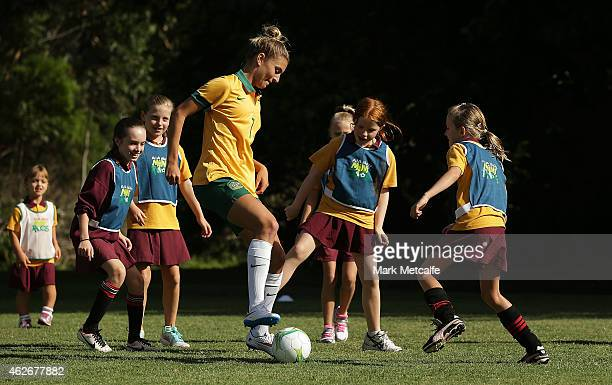 Steph Catley of the Matildas plays football with school children at the launch of MiniRoos kids football at Cohen Park Annandale on February 3 2015...
