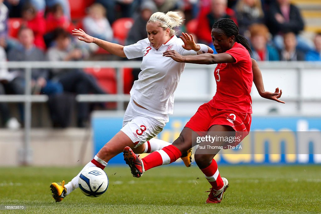 Steph Houghton of England in action with Tiffany Cameron (R) of Canada during the International friendly match between England and Canada at The New York Stadium on April 7, 2013 in Rotherham, England.
