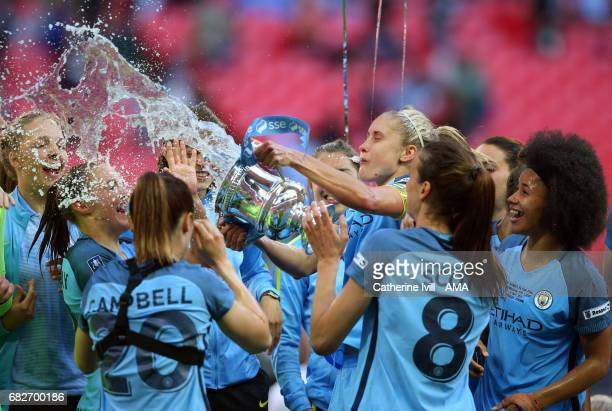 LONDON ENGLAND MAY 13 Steph Houghton of Manchester City Women throws champagne from the trophy at her team mates during the SSE Women's FA Cup Final...