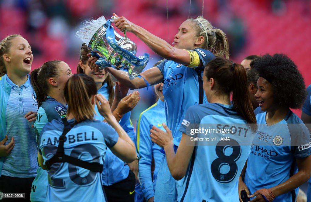 Steph Houghton of Manchester City Women throws champagne from the trophy over her team mates during the SSE Women's FA Cup Final between Birmingham City Ladies and Manchester City Women at Wembley Stadium on May 13, 2017 in London, England.