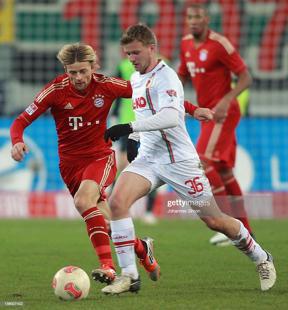 Stephan Hain (C) of Augsburg fights for the ball with Anatoliy Tymoshchuk (L) of Bayern during the Bundesliga match between FC Augsburg and FC Bayern Muenchen at SGL Arena on December 8, 2012 in Augsburg, Germany.