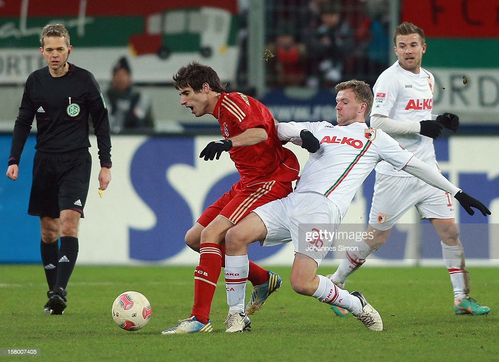 Stephan Hain (2R) of Augsburg fights for the ball with Javier Martinez (2L) of Bayern, watched by referee <a gi-track='captionPersonalityLinkClicked' href=/galleries/search?phrase=Jochen+Drees&family=editorial&specificpeople=801383 ng-click='$event.stopPropagation()'>Jochen Drees</a> (L) (R: <a gi-track='captionPersonalityLinkClicked' href=/galleries/search?phrase=Daniel+Baier&family=editorial&specificpeople=706624 ng-click='$event.stopPropagation()'>Daniel Baier</a> of Augsburg) during the Bundesliga match between FC Augsburg and FC Bayern Muenchen at SGL Arena on December 8, 2012 in Augsburg, Germany.