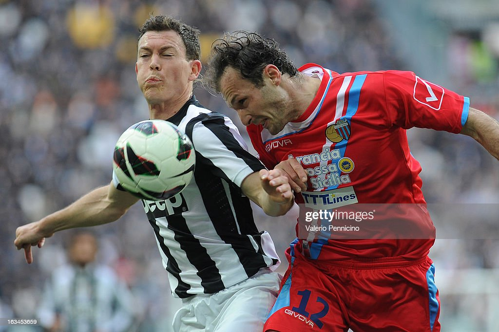 Stephan Lichtsteiner (L) of FC Juventus clashes with Giovanni Marchese of Calcio Catania during the Serie A match between FC Juventus and Calcio Catania at Juventus Arena on March 10, 2013 in Turin, Italy.