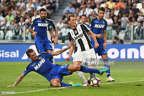 Stephan Lichtsteiner of Juventus FC is tackled by Francesco Acerbi of US Sassuolo during the Serie A match between Juventus FC and US Sassuolo at...