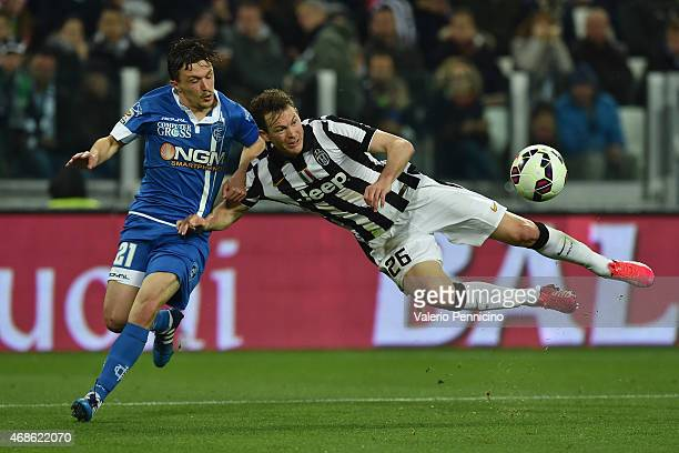 Stephan Lichtsteiner of Juventus FC is tackled by Mario Rui of Empoli FC during the Serie A match between Juventus FC and Empoli FC at Juventus Arena...