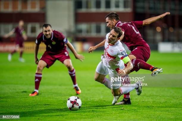 Stephan Lichtsteiner of Switzerland is fouled by Vitalijs Maksimenko of Latvia during the FIFA 2018 World Cup Qualifier between Latvia and...