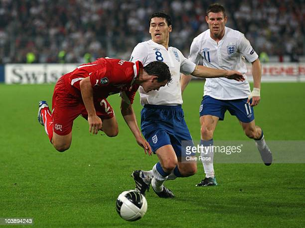 Stephan Lichtsteiner of Switzerland is tackled by Gareth Barry of England during the EURO 2012 Group G Qualifier between Switzerland and England at...