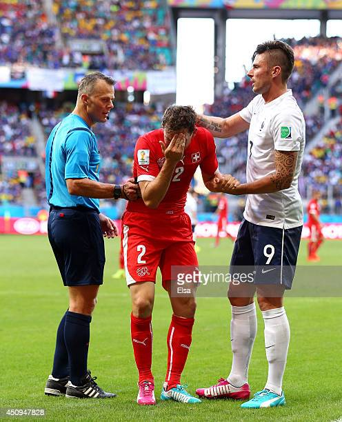 Stephan Lichtsteiner of Switzerland speaks to referee Bjorn Kuipers after a collision with Olivier Giroud of France during the 2014 FIFA World Cup...