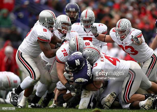 Stephan Simmons of the Northwestern Wildcats is tackled by Nate Williams and Dexter Larimore of the Ohio State Buckeyes at Ryan Stadium on November 8...
