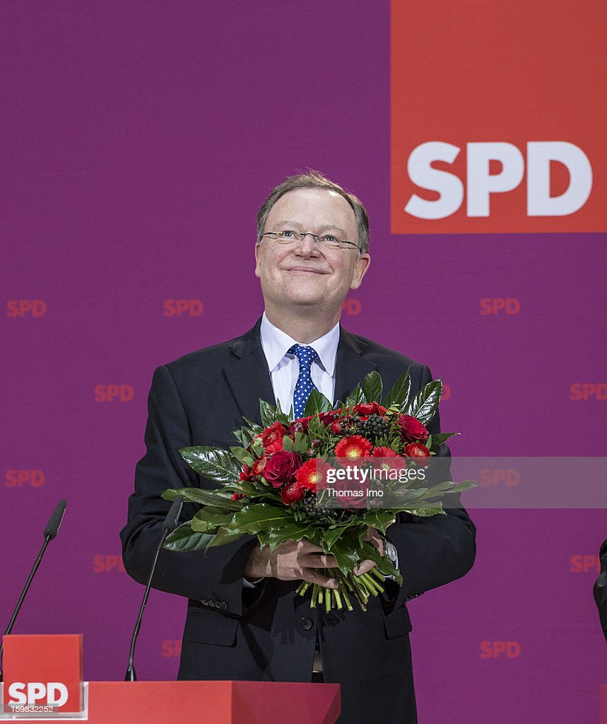 Stephan Weil, candidate in Lower Saxony for the German Social Democrats (SPD), holds a buquet of flowers during a press conference the day after the SPD and German Greens party emerged with a hairline victory in Lower Saxony on January 21, 2013 in Berlin, Germany. The win has given the SPD a much needed boost following declining popularity figures for its chancellor candidate Peer Steinbrueck. Germany faces national elections later this year.