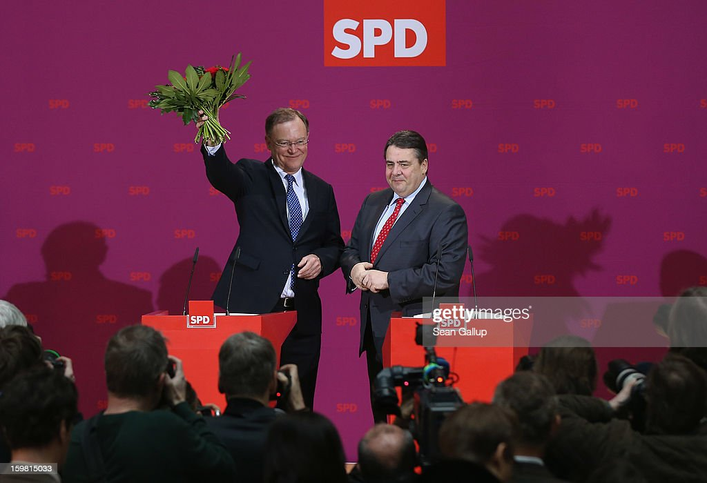 Stephan Weil, gubernatorial candidate in Lower Saxony for the German Social Democrats (SPD), holds up flowers he received from SPD Chairman Sigmar Gabriel the day after the SPD and German Greens party emerged with a hairline victory in Lower Saxony on January 21, 2013 in Berlin, Germany. The win has given the SPD a much needed boost following declining popularity figures for its chancellor candidate Peer Steinbrueck. Germany faces national elections later this year.