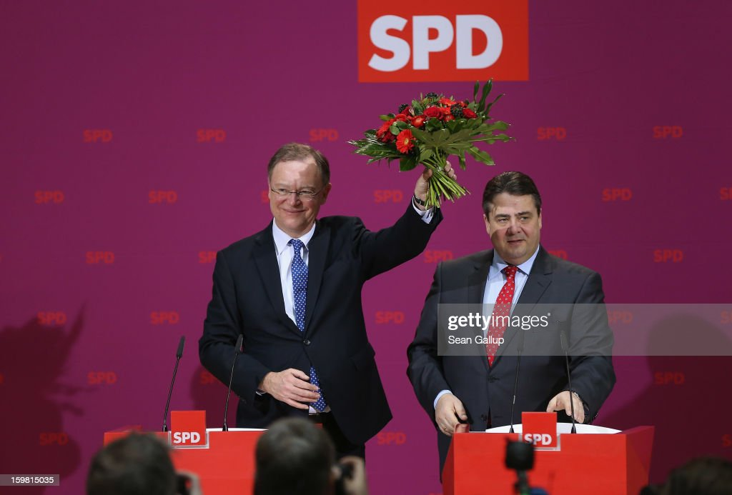Stephan Weil, gubernatorial candidate in Lower Saxony for the German Social Democrats (SPD), holds up flowers he received from SPD Chairman <a gi-track='captionPersonalityLinkClicked' href=/galleries/search?phrase=Sigmar+Gabriel&family=editorial&specificpeople=543927 ng-click='$event.stopPropagation()'>Sigmar Gabriel</a> the day after the SPD and German Greens party emerged with a hairline victory in Lower Saxony on January 21, 2013 in Berlin, Germany. The win has given the SPD a much needed boost following declining popularity figures for its chancellor candidate Peer Steinbrueck. Germany faces national elections later this year.