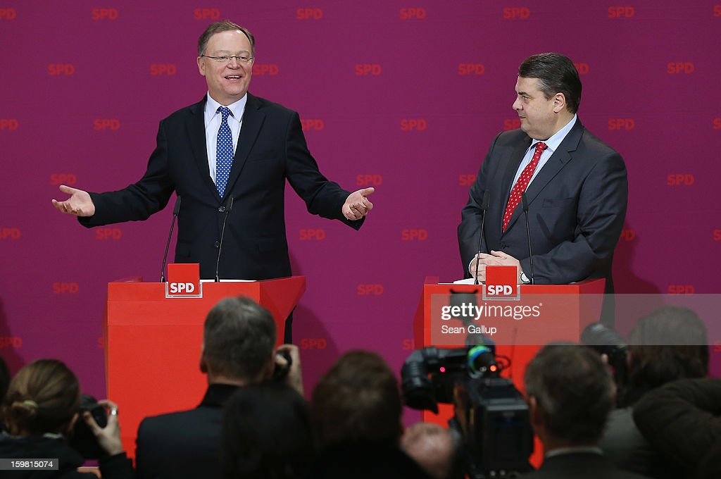 Stephan Weil (L), gubernatorial candidate in Lower Saxony for the German Social Democrats (SPD), speaks with SPD Chairman <a gi-track='captionPersonalityLinkClicked' href=/galleries/search?phrase=Sigmar+Gabriel&family=editorial&specificpeople=543927 ng-click='$event.stopPropagation()'>Sigmar Gabriel</a> to reporters and SPD members at SPD headquarters the day after the SPD and German Greens party emerged with a hairline victory in Lower Saxony on January 21, 2013 in Berlin, Germany. The win has given the SPD a much needed boost following declining popularity figures for its chancellor candidate Peer Steinbrueck. Germany faces national elections later this year.