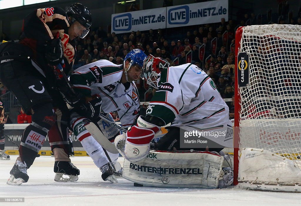 Stephan Wilhelm (L) of Hannover and Justin Forrest (C) of Augsburg battle for the puck in front of the net during the DEL match between Hannover Scorpions and Augsburger Panther at TUI Arena at TUI Arena on January 9, 2013 in Hanover, Germany.