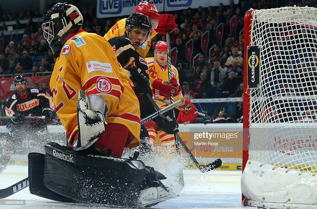 Stephan Wilhlem (C) of Hannover fails to score over Felix Bick (L), goaltender of Duesseldorf during the DEL match between Hannover Scorpions and Duesseldorfer EG at TUI Arena on February 1, 2013 in Hanover, Germany.