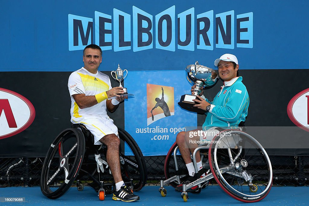 Stephane Houdet of France poses with his runners-up trophy along side Shingo Kunieda of Japan withthe championship trophy after the Men's Wheelchair Singles Final match during the 2013 Australian Open Wheelchair Championships at Melbourne Park on January 26, 2013 in Melbourne, Australia.