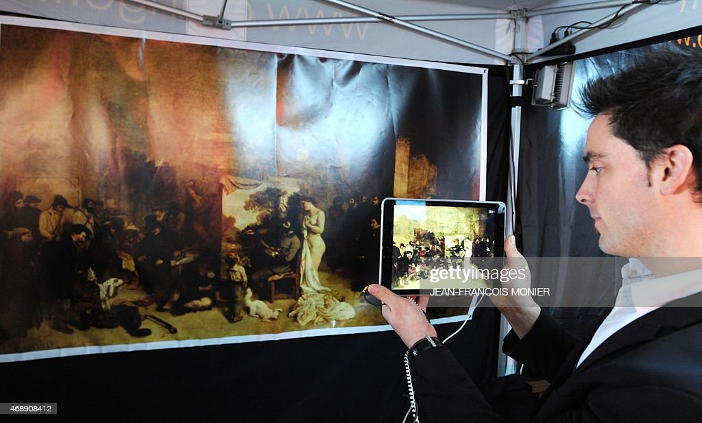 Stephane Le Gall, developer of augmented reality software, uses a tablet to 'walk' into in a copy of the painting by <a gi-track='captionPersonalityLinkClicked' href=/galleries/search?phrase=Gustave+Courbet&family=editorial&specificpeople=98922 ng-click='$event.stopPropagation()'>Gustave Courbet</a>, 'The Painter's Workshop', on April 8, 2015, in Laval, western France. The 27 square meter painting is at the the D'Orsay Museum in Paris and is currently being restored, but visitors will still be able to enjoy viewing it using the software developed in partnership with the Orange group. The latest technology and the most innovative applications in the field of the virtual reality, augmented reality, and 3D real time will be exhibited at the Framework, in Laval, until April 12. AFP PHOTO / JEAN-FRANCOIS MONIER