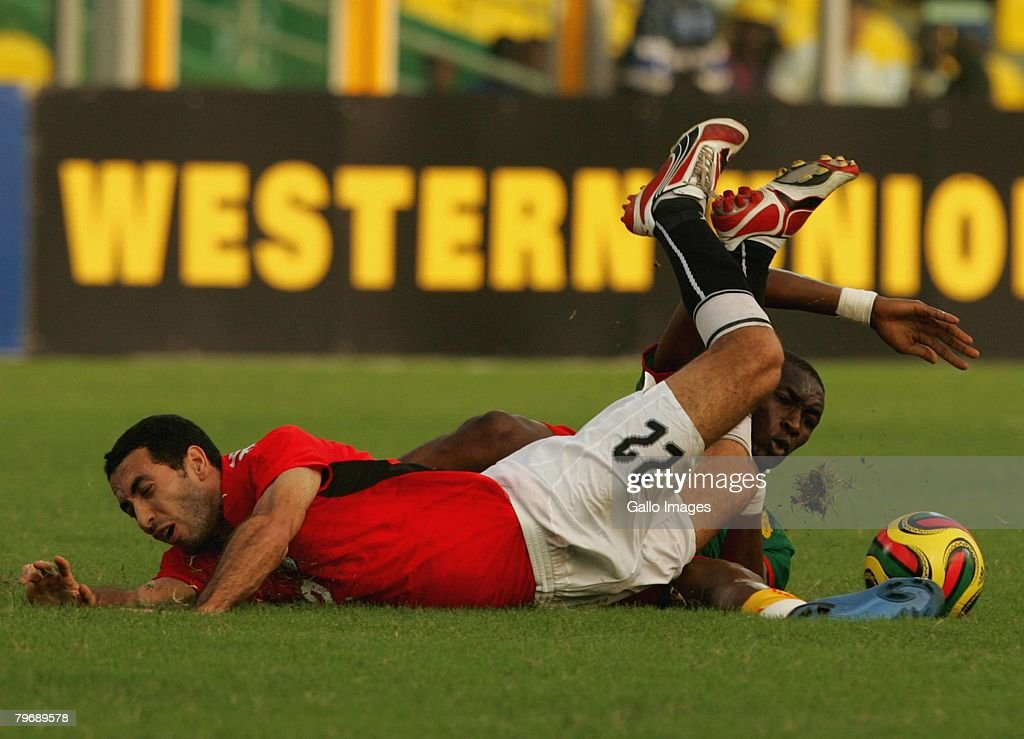 Stephane Mbia of Cameroon competes with Mohamed Abouterika of Egypt during the AFCON Final between Egypt and Cameroon at the Ohene Djan stadium on...