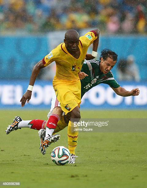 Stephane Mbia of Cameroon has his jersey pulled as he is challenged by Andres Guardado of Mexico during the 2014 FIFA World Cup Brazil Group A match...