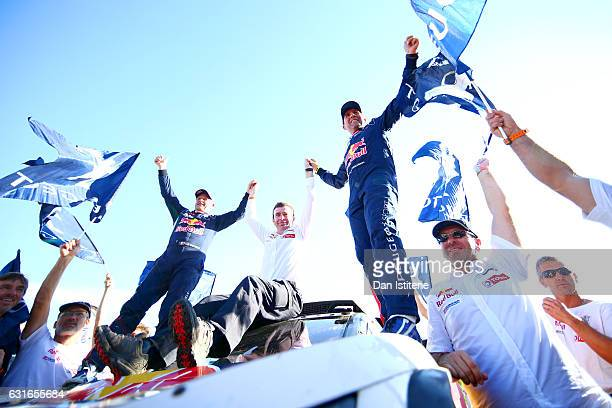 Stephane Peterhansel of France and Peugeot Total and his codriver Jean Paul Cottret of France celebrate with Bruno Famin Peugeot Sport Director at...