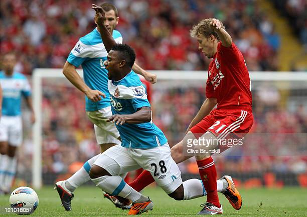 Stephane Sessegnon of Sunderland is tackled by Leiva Lucas of Liverpool during the Barclays Premier League match between Liverpool and Sunderland at...