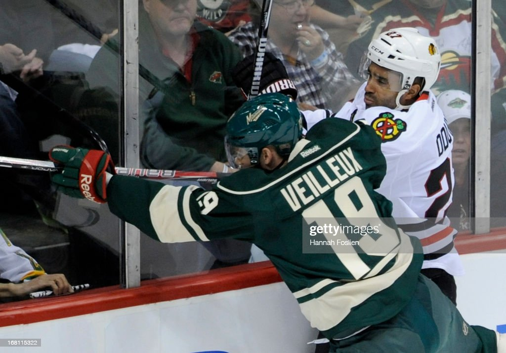 Stephane Veilleux #19 of the Minnesota Wild checks Johnny Oduya #27 of the Chicago Blackhawks into the boards during the first period of Game Three of the Western Conference Quarterfinals during the 2013 NHL Stanley Cup Playoffs at Xcel Energy Center on May 5, 2013 in St Paul, Minnesota.