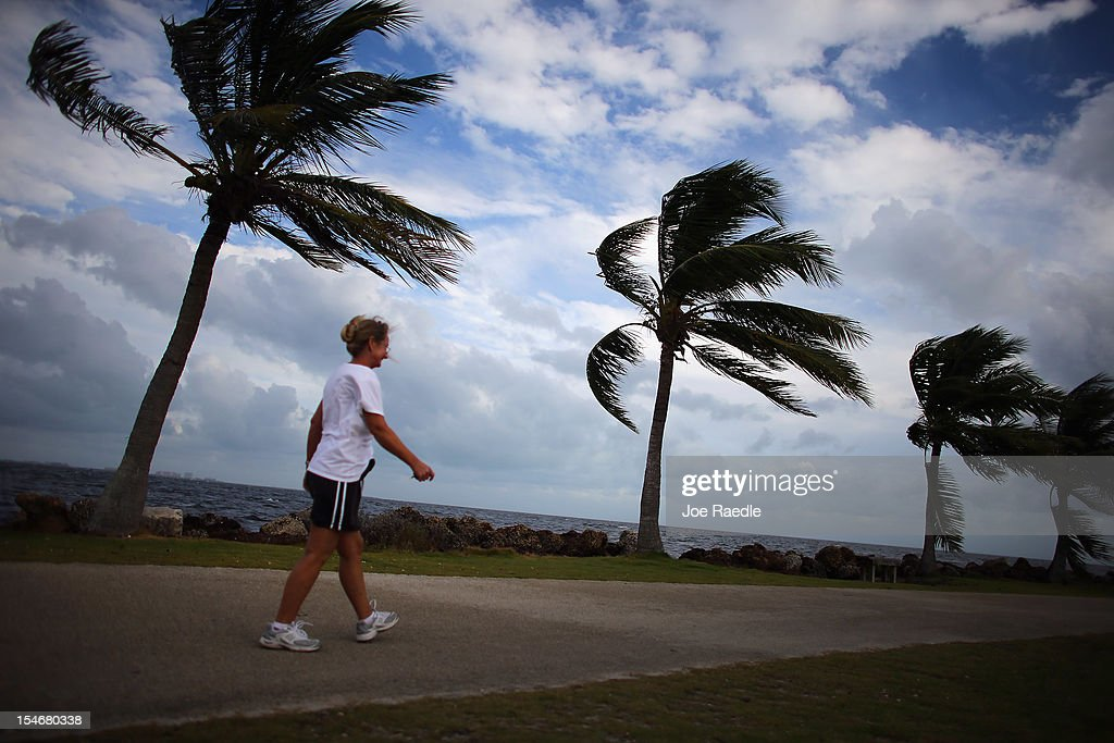 Stephanie Bilyeu walks along the ocean as blustery winds blow through the palm trees as the outerbands of Hurricane Sandy are felt on October 24, 2012 in Miami, Florida. After passing over Jamaica, Sandy is expected to hit eastern Cuba on Wednesday night and into the Bahamas Thursday and Friday, a tropcial storm warning was issued for east coast of Florida from Ocean Reef to Sebasian Inlet and a tropical storm watch was extended along the east coast to Flagler Beach.