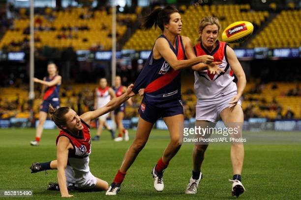 Stephanie Chiocci of Diamond Creek handpasses whilst being tackled by Karen Paxman of Darebin and Annalyse Lister of Darebin during the VFL Women's...