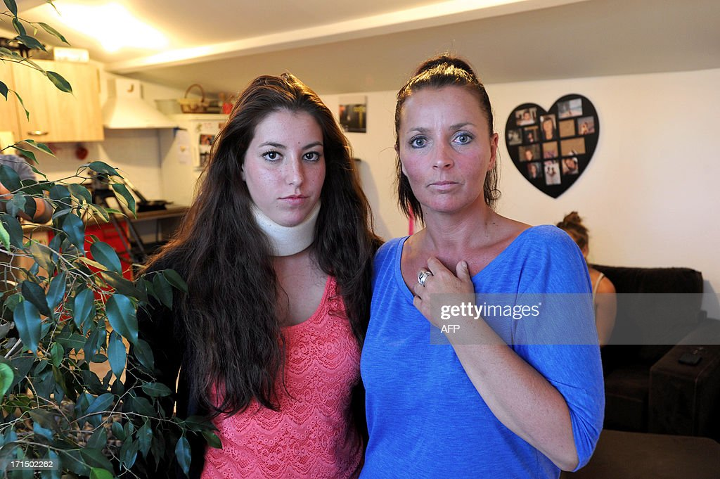Stephanie Couturier and her daughter Tiphaine, pose at their home in La Rochelle on June 25, 2013, two weeks after the 15 year-old girl was beaten up by school children who posted the agression on Facebook. Tiphaine, who suffers from whiplash and a broken rib, filed a complaint. AFP PHOTO / XAVIER LEOTY