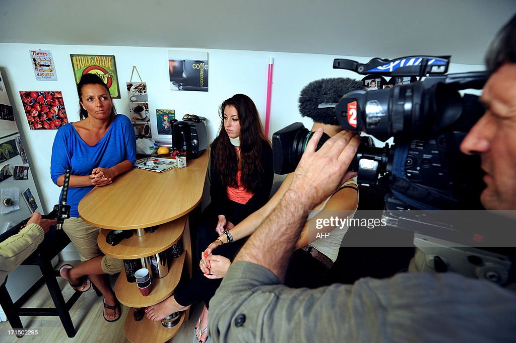 Stephanie Couturier and her daughter Tiphaine, pose at their home in La Rochelle on June 25, 2013, two weeks after the 15 year-old girl was beaten up by school children who posted the agression on Facebook. Tiphaine, who suffers from whiplash and a broken rib, filed a complaint.