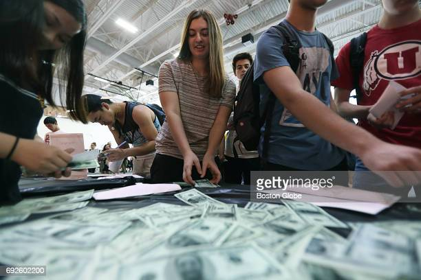 Stephanie Ethier center and Ming Tam far left play the life skills game at the Newton North High School Financial Reality Fair in Newton MA on May 19...