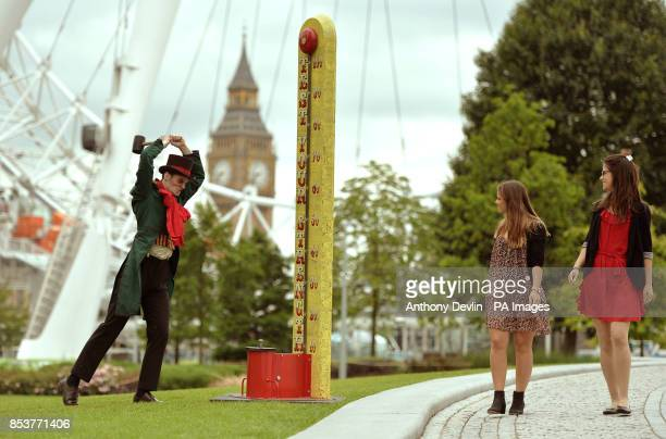 Stephanie Francis and Tansy RatcliffeJames lookon as man in costume tests his strength on the High Striker during a photo call for the London...