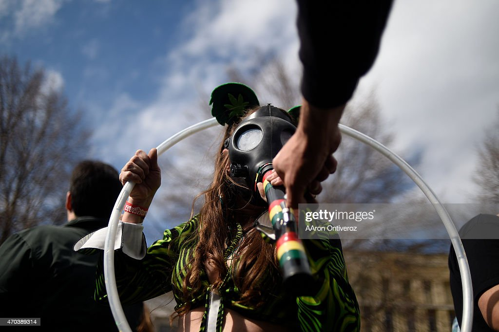 Stephanie Hodge smokes a gas mask marijuana smoking apparatus as Jesse Wright lights it during Denver's annual 4/20 festival at Civic Center Park on Sunday, April 19, 2015. Thousands of people gathered to watch a free Rick Ross concert, while partaking in the day's goods and services.